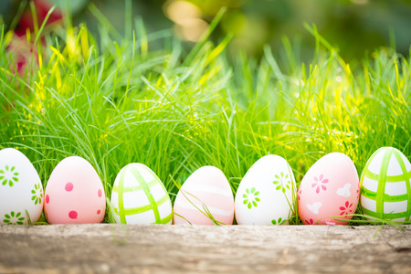 Easter eggs in grass against blurred green background. Spring holidays concept Zdjęcie Seryjne