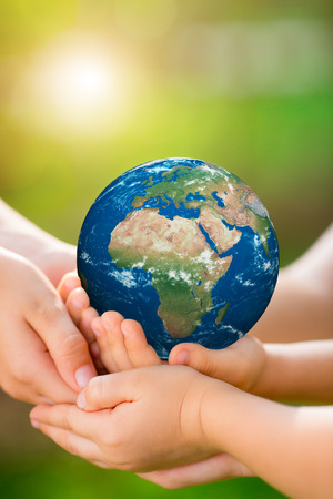 Children holding 3D planet in hands against green spring background. Earth day holiday concept.  Stock Photo