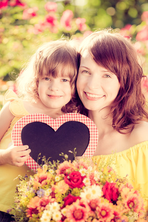 Happy woman and child with beautiful spring flowers against green background. Family holiday concept. Mothers day photo