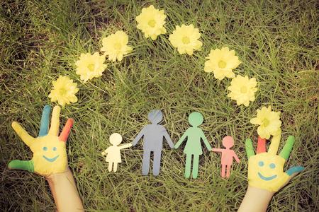 Groep van gelukkige mensen op groen gras. Familie die pret in het voorjaar. Smiley op handen. Ecologisch concept. Bovenaanzicht portret. Retro getinte afbeelding
