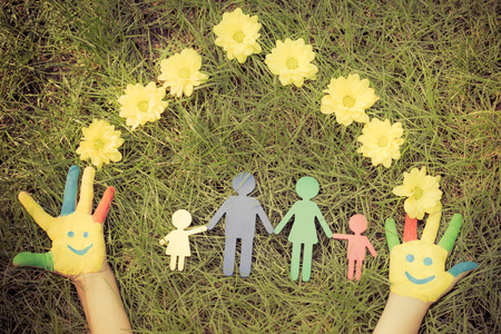 family: Group of happy people on green grass. Family having fun in spring. Smiley on hands. Ecology concept. Top view portrait. Retro toned image