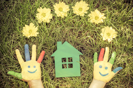 earth day: Group of happy people on green grass. Family having fun in spring. Smiley on hands. Ecology concept. Top view portrait. Retro toned image