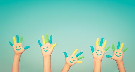cara sonriente: Gente feliz con sonriente en las manos contra el cielo azul de fondo verano