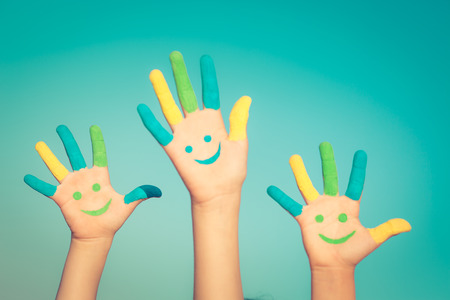 Happy children with smiley on hands against blue summer sky background Stock Photo