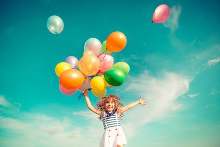 Gelukkig kind springen met kleurrijke speel goed ballonnen buiten. Lachende jongen plezier in groene lente veld tegen blauwe hemel achtergrond. Vrijheid concept