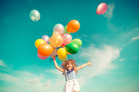 fit girl: Happy child jumping with colorful toy balloons outdoors. Smiling kid having fun in green spring field against blue sky background. Freedom concept
