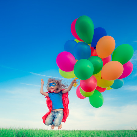 fun: Happy superhero child jumping with colorful toy balloons outdoors. Smiling kid having fun in green spring field against blue sky background. Freedom concept