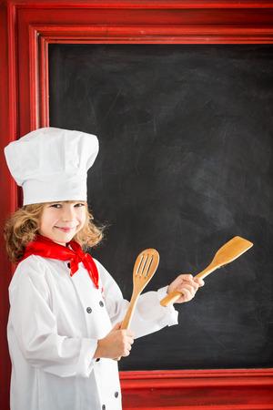 Kind chef-kok tegen bord leeg menu met tekenen van gezond voedsel. Restaurant business concept Stockfoto