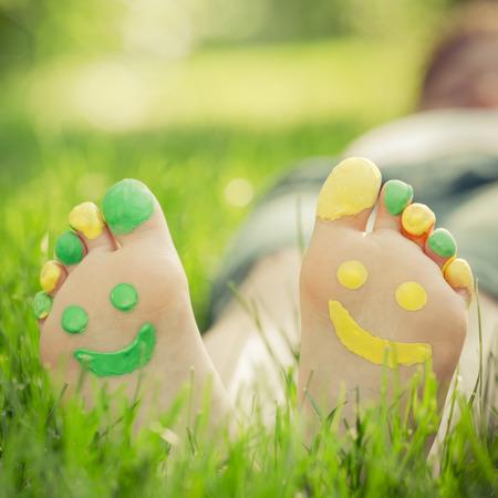 pies descalzos: Niño acostado en la hierba verde. Cabrito que se divierte al aire libre en el parque del resorte