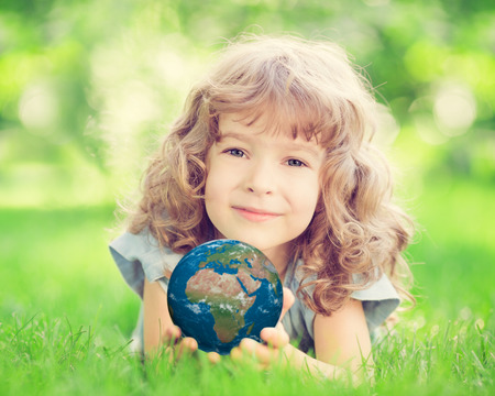 environment protection: Child holding 3D planet in hands against green spring background. Earth day holiday concept. Elements of this image furnished by NASA