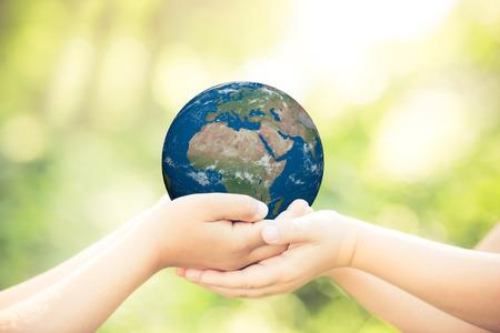happy planet earth: Ni�os que sostienen planeta 3D en manos contra el fondo verde de la primavera. Concepto de vacaciones de D�a de la Tierra. Los elementos de esta imagen proporcionada por la NASA Foto de archivo