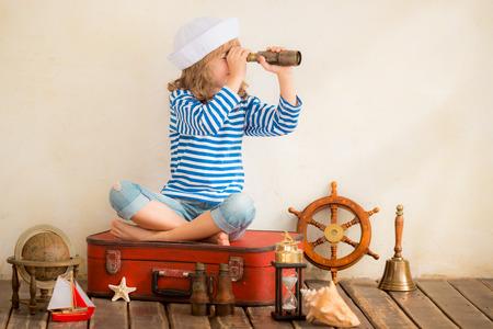 marinero: Niño feliz que juega con las cosas náuticas vintage. Cabrito que se divierte en el país. Verano de ensueño del mar y de la imaginación. Aventura y el concepto de viaje. Imagen en tonos retro