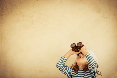Niño feliz que juega con los prismáticos náuticos de la vendimia. Cabrito que se divierte en el país. Verano de ensueño del mar y de la imaginación. Aventura y el concepto de viaje. Imagen en tonos retro