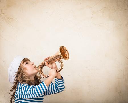 Šťastné dítě foukání vintage námořní roh. Kid baví doma. Letní moře sen a fantazie. Adventure a cestovní koncept. Retro tónovaný obraz