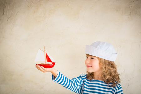 Glückliches Kind, das mit Vintage Holz Spielzeug Schiff. Kid Spaß zu Hause. Sommer Meer Traum und Phantasie. Abenteuer und Reise-Konzept. Retro getönten Bild Standard-Bild - 37939405
