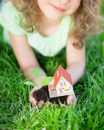 Child holding house and tree in hands against spring green background. Real estate concept Stock Photo
