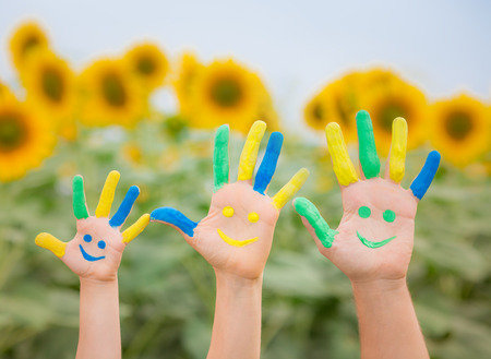 Happy family with smiley on hands against blue sky and yellow sunflower background photo