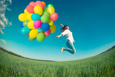 Happy girl jumping with colorful toy balloons outdoors. Young woman having fun in green spring field against blue sky background. Freedom concept