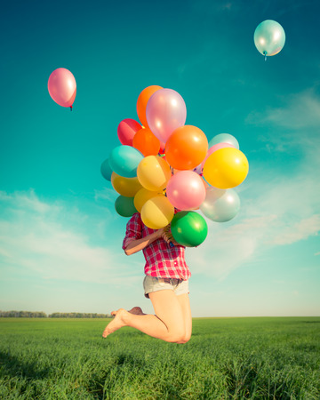 Happy girl jumping with colorful toy balloons outdoors. Young woman having fun in green spring field against blue sky background. Freedom concept photo