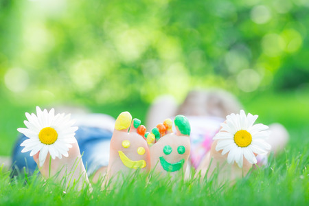 Couple lying on green grass. Children having fun outdoors in spring park Archivio Fotografico