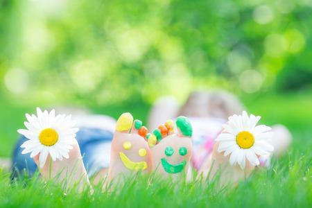 enfant qui joue: Couple couché sur l'herbe verte. Les enfants se amusent en plein air dans le parc de printemps Banque d'images