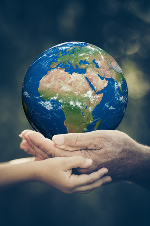 globe in hand: Child and senior holding 3D planet in hands against green spring background. Earth day holiday concept. Elements of this image furnished by NASA