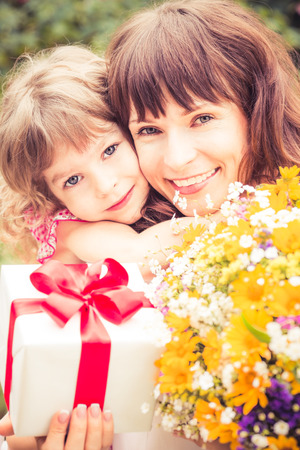 Happy woman and child with beautiful spring flowers against green background. Family holiday concept. Mothers day