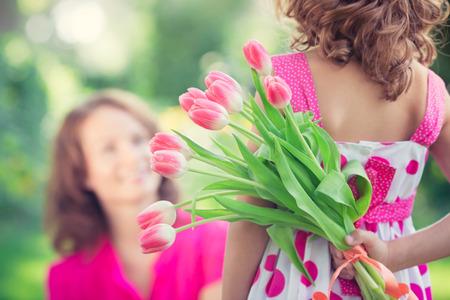fraue: Frau und Kind mit Blumenstrauß vor grünem Hintergrund unscharf. Frühling Familienurlaub Konzept. Frauen heute