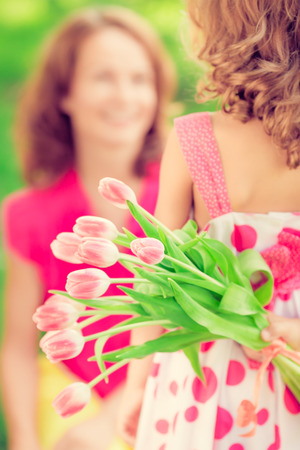 Woman and child with bouquet of flowers against green blurred background. Spring family holiday concept. Womens day Imagens