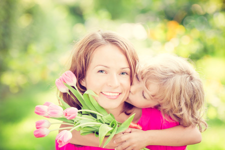 Woman and child with bouquet of flowers against green blurred background. Spring family holiday concept. Womens day Zdjęcie Seryjne