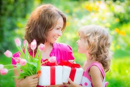 Vrouw en kind met boeket van bloemen tegen groene achtergrond wazig. Spring vakantie met het gezin concept. Vrouwendag Stockfoto