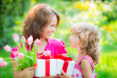 Woman and child with bouquet of flowers against green blurred background. Spring family holiday concept. Women's day Stock Photo