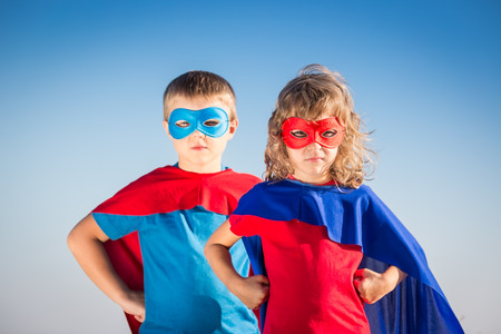 super powers: Superhero children against summer sky background. Kids having fun outdoors. Boy and girl playing. Success and winner concept Stock Photo