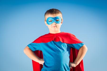 Superhero boy against summer sky background. Success and winner concept