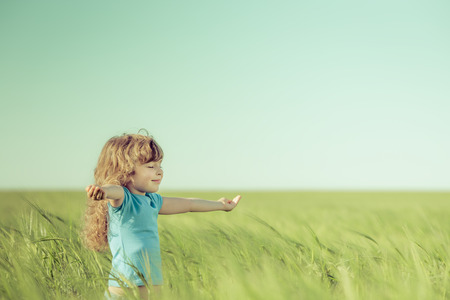 outdoors: Happy child in spring field. Young girl relax outdoors. Freedom concept