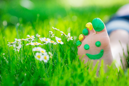 pies descalzos: Ni�o acostado en la hierba verde. Cabrito que se divierte al aire libre en el parque del resorte
