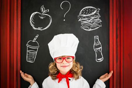 niños cocinando: Cocinar del cocinero del niño contra menú pizarra en blanco con el dibujo de una alimentación sana. Restaurante concepto de negocio Foto de archivo