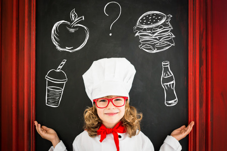 Child chef cook against blackboard blank menu with drawing healthy food. Restaurant business concept Standard-Bild