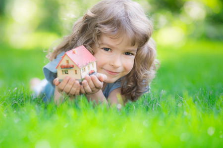 Happy child holding model house in hands. Kid lying on green grass in spring park. New home concept