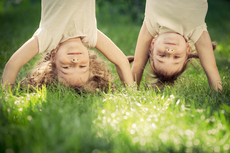 Happy children standing upside down on green grass. Smiling kids having fun in spring park. Healthy lifestyle concept Stockfoto