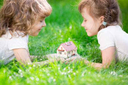 Happy children holding model house in hands. Kids lying on green grass in spring park. New home concept 版權商用圖片 - 38104179