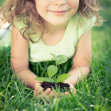 Child holding young green plant in hands. Kid lying on grass in spring park. Earth day concept