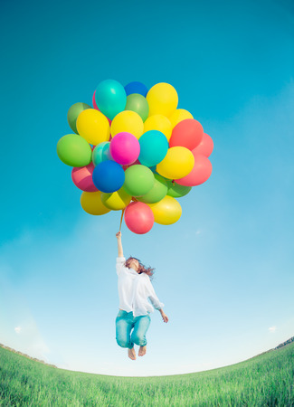 balloons green: Happy girl jumping with colorful toy balloons outdoors. Young woman having fun in green spring field against blue sky background. Freedom concept