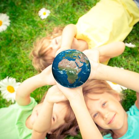happy planet earth: Ni�os que sostienen planeta 3D en manos contra el fondo verde de la primavera. Concepto de vacaciones de D�a de la Tierra.