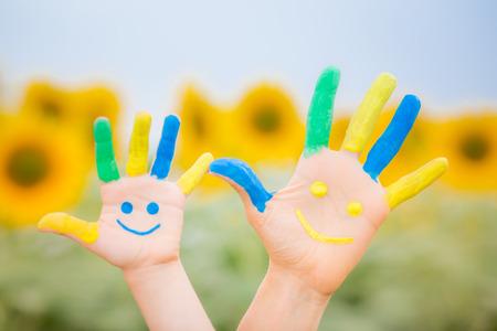 konzepte: Glückliche Familie mit Smiley auf Händen gegen den blauen Himmel und gelben Sonnenblumen Hintergrund