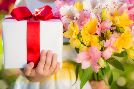 Gift box and flowers in hands against spring background. Family holiday concept. Mothers day