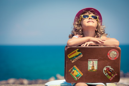 children face: Child with vintage suitcase on summer vacation. Travel and adventure concept Stock Photo