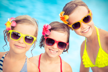 family portrait: Happy children in the swimming pool. Funny kids playing outdoors. Summer vacation concept