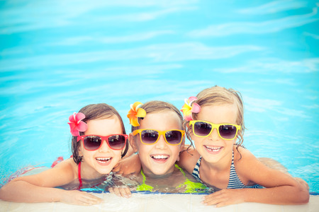niños sanos: Felices los niños en la piscina. Niños divertidos jugando al aire libre. Concepto de las vacaciones de verano