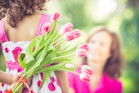 Mother and daughter with bouquet of flowers against green blurred background. Spring family holiday concept. Mother's day